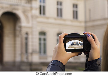 Tourist's hands holding photo camera and taking picture