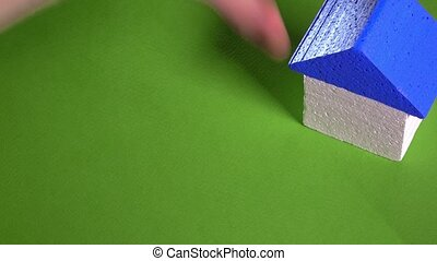 Realtor placing toy house with blue roof and holding small...
