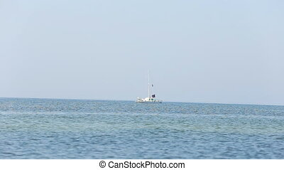 yacht on the sea - small boat slowly floats on the sea