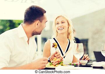 happy couple eating dinner at restaurant terrace