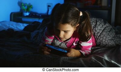 teen girl playing a portable video game console kid at night...
