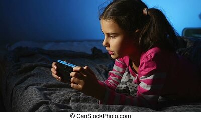 teen girl playing portable video game a console kid at night...