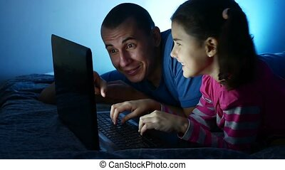 Teen girl and man father and daughter working at laptop, the...