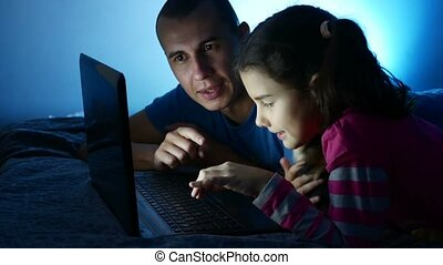 Teen girl and man father and daughter working at laptop,...