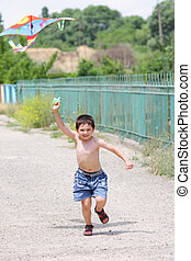 Little boy flying kite - Little smiling boy flying kite on...