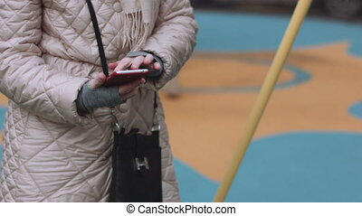 Woman using smart phone - Female in winter outfit standing...
