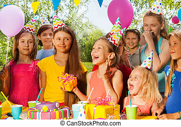 Group of excited kids congratulating birthday girl