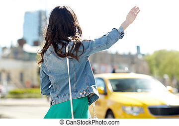 young woman or girl catching taxi on city street - gesture,...