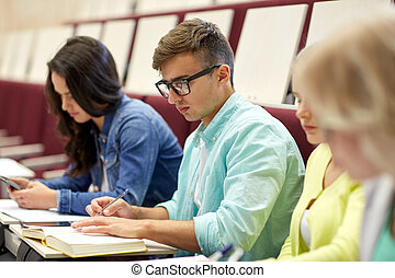group of students with books writing at lecture
