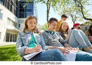 group of students with notebooks at school yard - education,...