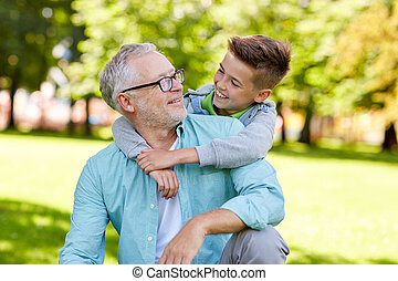 grandfather and grandson hugging at summer park - family,...