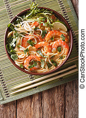 Malaysian laksa soup with shrimps, noodles and herbs close...