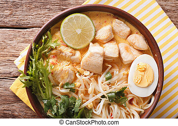 Malaysian laksa soup with chicken close up in a bowl....