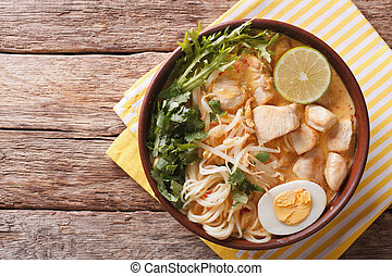 Malaysian laksa soup with chicken, egg, noodles and herbs...