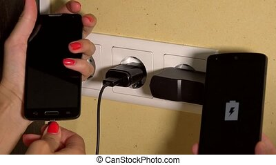 Man and woman hands hold charging smart phones connected to...