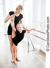 Ballerina and her teacher stretching legs in ballet studio