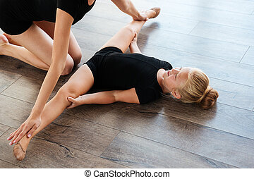 Little girl doing stretching exercises with her teacher -...