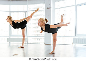 Woman and little girl ballerina dancing in ballet school