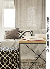Living room with pattern pouf, sofa and  table
