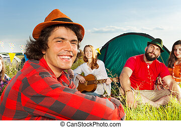 Cute young man in hat sitting with friends at camp