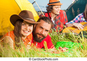 Young couple lying on the grass next to their tent -...