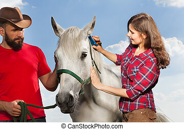 Young woman brushing beautiful white horse while man in...