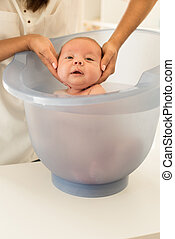 Baby bath time - Adorable newborn baby having a bath by the...