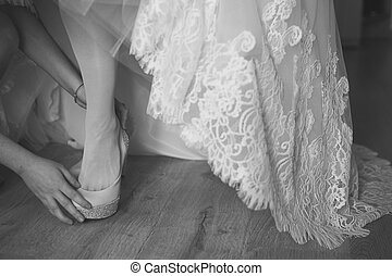 bridesmaid helping bride to put on elegant shoes Black and...