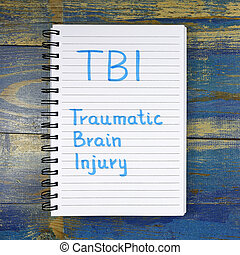 TBI- Traumatic Brain Injury acronym written in notebook on...