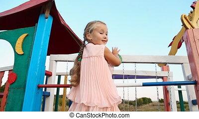 little girl waving - little girl waves her hand sitting on...