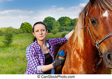 Portrait of young woman brushing beautiful horse - Portrait...