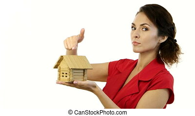 Angry woman holding a little house in her hands and destroy home