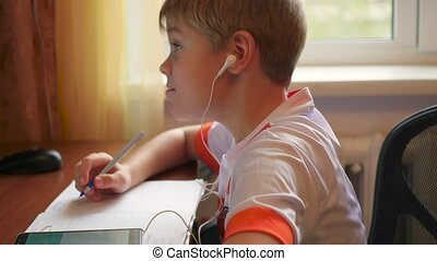 the child listens to music on smartphone in the headphones making lessons