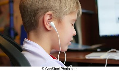 the child listens to music on smartphone in the headphones in home