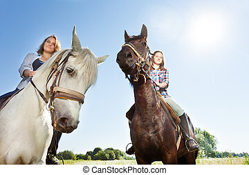 Two happy women riding beautiful purebred horses