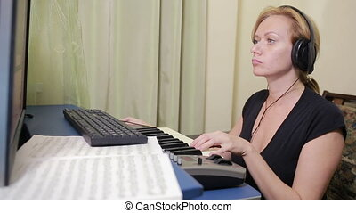 woman writes music on the computer. digital piano midi...
