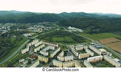 Aerial view, apartment buildings surrounded by hills....