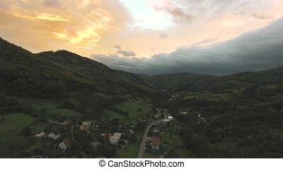 Aerial view of village surrounded by wood, sunset. Nova...