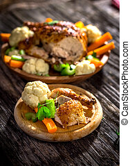 Whole roasted chicken with vegetables on wooden background