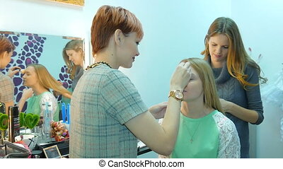 Make-up artist and stylist doing makeup model for...