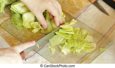 hands slicing iceberg lettuce - Female hands slicing iceberg...