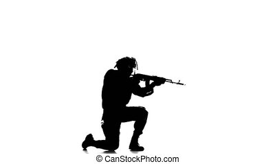 Soldier stands on one knee and taking aim at the distance....