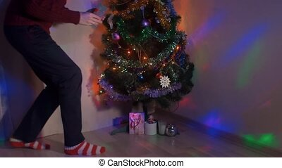 Young man sneaking up to Christmas tree placing gift...