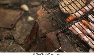 Sausages wrapped in bacon cooking on the grill. Camera...