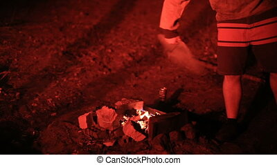 man blows the coals in the forest at night