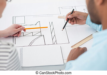 Two architects discussing details of blueprint
