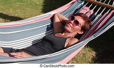 Woman resting in a hammock - A middle aged woman resting in...