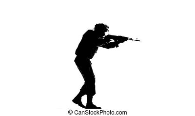 Man walks slowly with a gun in the hands. Silhouette - Man...