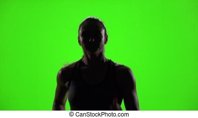 Athletic fitness woman running. Front view. Green screen....