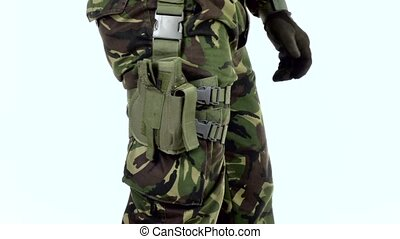 Soldier put the gun in the holster. White backgraund -...